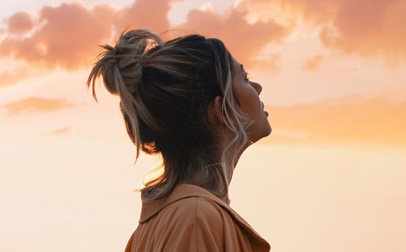 Chica rubia con coleta mirando el cielo en el atardecer