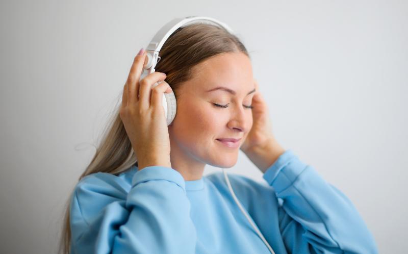 Chica rubia con auriculares escucha música con los ojos cerrados