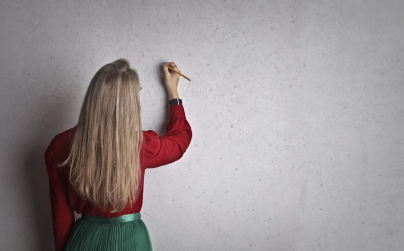 Chica escribiendo en una pizarra en blanco