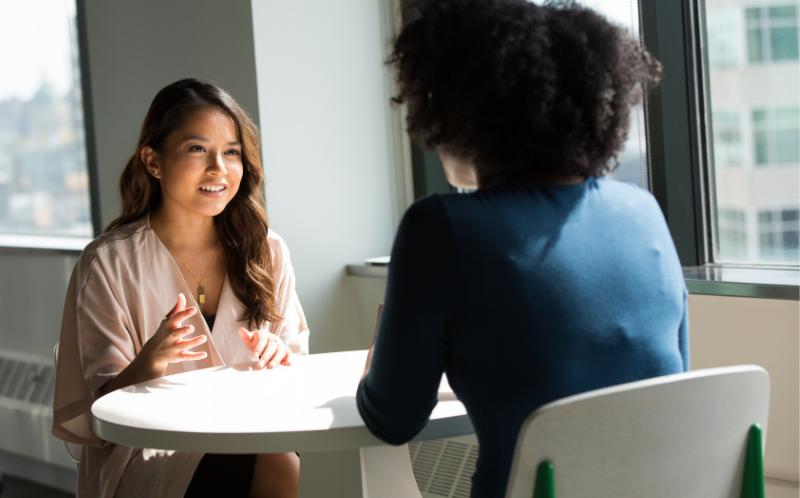 Chicas conversando sentadas a una mesa.