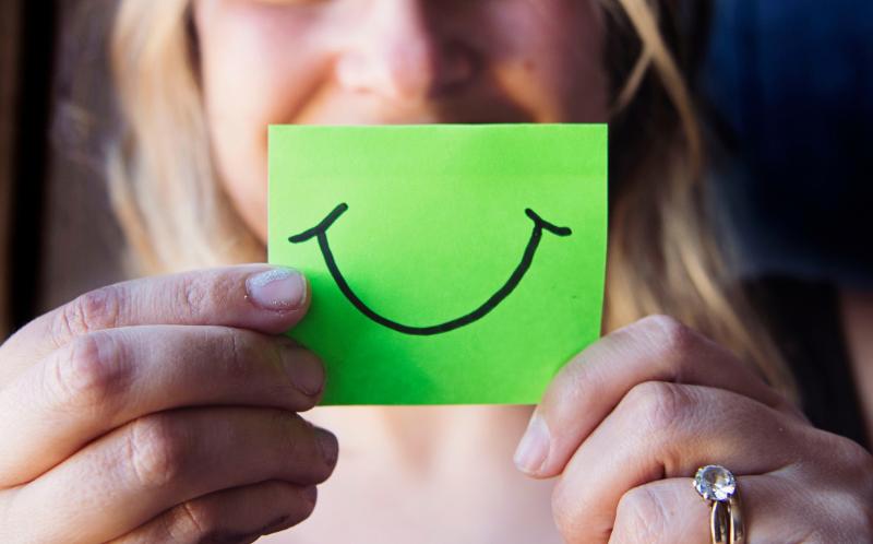 Chica sujetando un post-it con cara sonriente dibujada