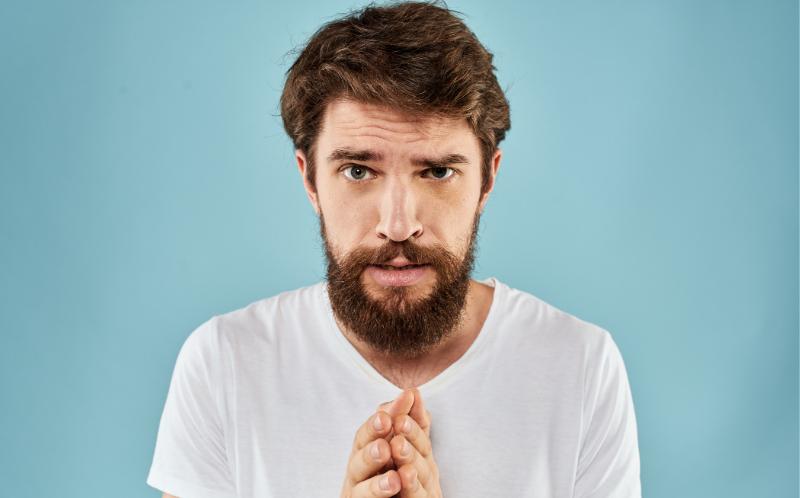 Chico con barba con gesto de arrepentimiento