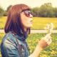 Chica con gafas de sol sujeta una flor con una mano mientras la sopla