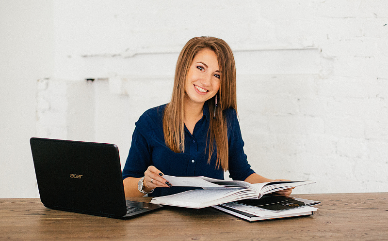 Chica sentada en una mesa con un ordenador portátil y unos libros