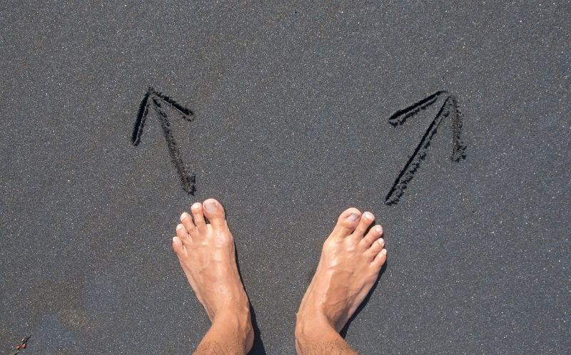 Pies en la playa con flechas marcado dos direcciones
